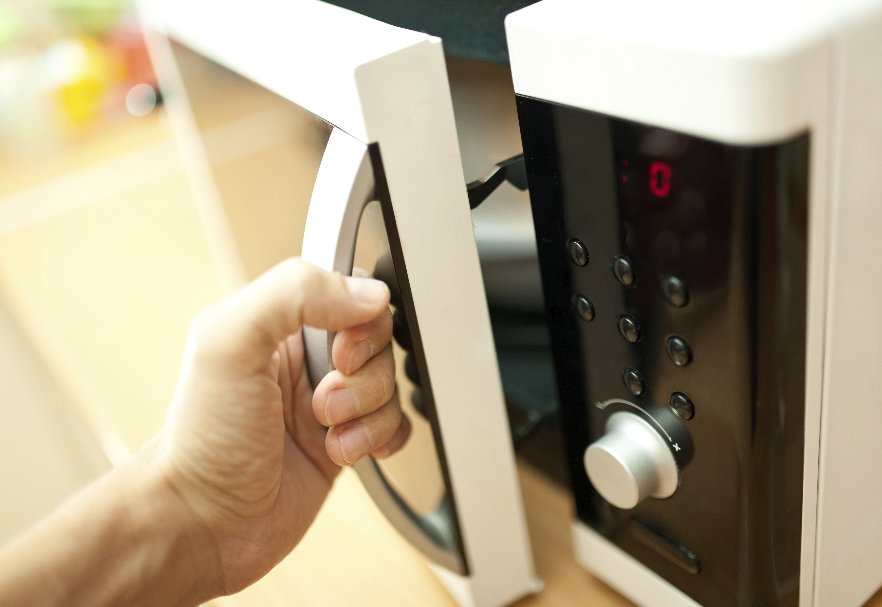 man opening the door of a microwave